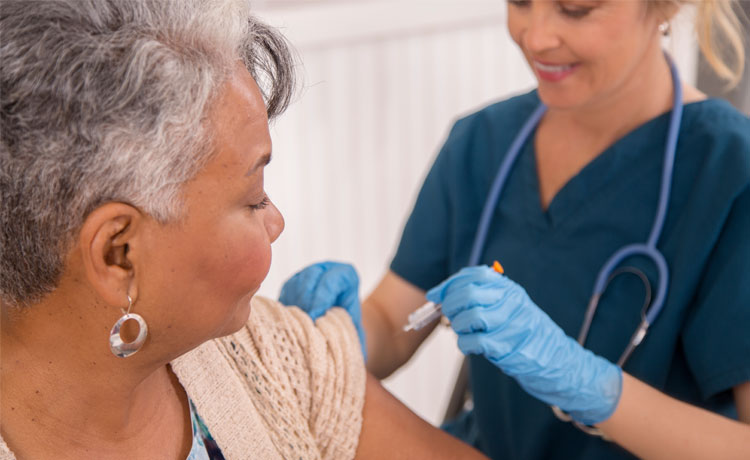 nurse gives senior the flu vaccine