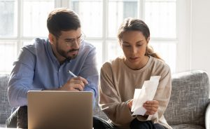 Serious couple calculating expenses, bills together, using laptop